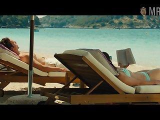 Emilia Clarke in swim put up is sunbathing by the poolside